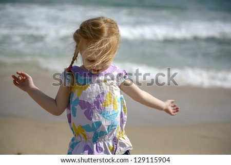 Red hair baby girl enjoying the wind, sun and ocean on a Miami Beach. Florida, USA. - stock photo