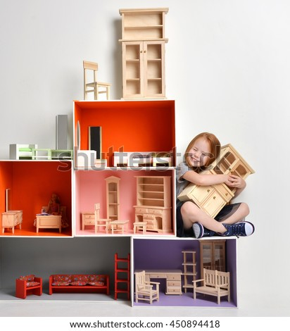 Red hair Baby Girl Kid playing with doll house stuffed with mini furniture toys and doll sitting on a cube in play room at home or kindergarten hugging little cabinet happy smiling