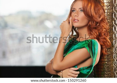 Red hair beauty Beautiful young red hair woman holding her hand on chin and looking away - stock photo