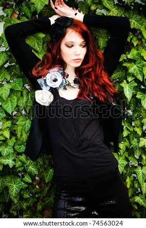 red hair fashion woman in black with fashion accessories agains wall with green rambler plant - stock photo