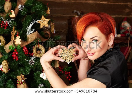 Red hair girl holding heart in her hands in a country house with wooden walls with christmas tree and a lot of presents