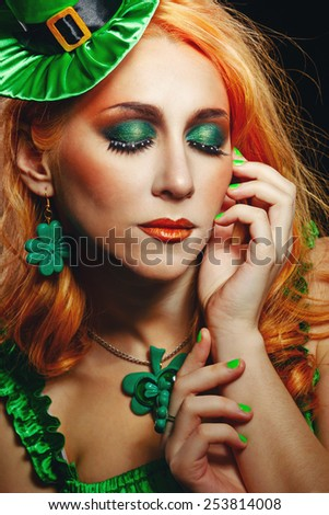 Red hair girl in Saint Patrick's Day leprechaun party hat having fun - stock photo
