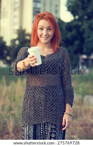 Red hair woman drinking tea or coffee from a white paper disposable cup. Concept - tea or coffee cup. Stretching forward with coffee cup. Young beautiful girl on the background of nature city park.  - stock photo