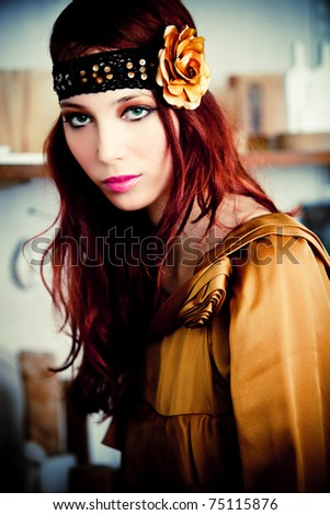 red hair woman in golden dress and headband with golden rose, indoor shot - stock photo