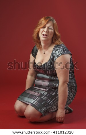 red hair woman, on her knees, throwing a tantrum - stock photo
