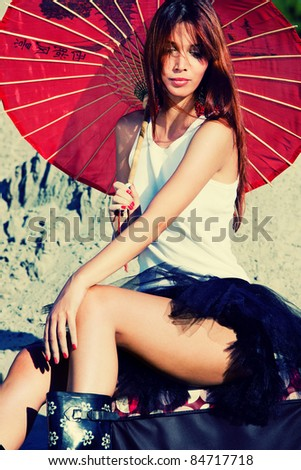 red hair woman portrait in desert with parasol - stock photo