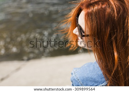 red hair young girl  sitting on a dock  - stock photo
