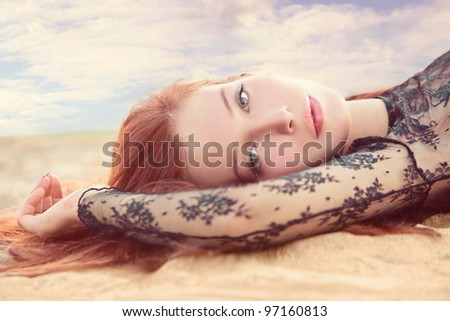 red hair young woman portrait in sand against summer sky with clouds small amount of grain added - stock photo