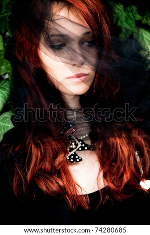 red hair young woman with black veil over face, outdoor shot - stock photo
