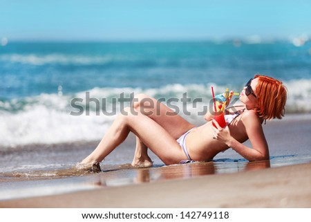 red-haired beautiful girl drinking cocktail on the beach