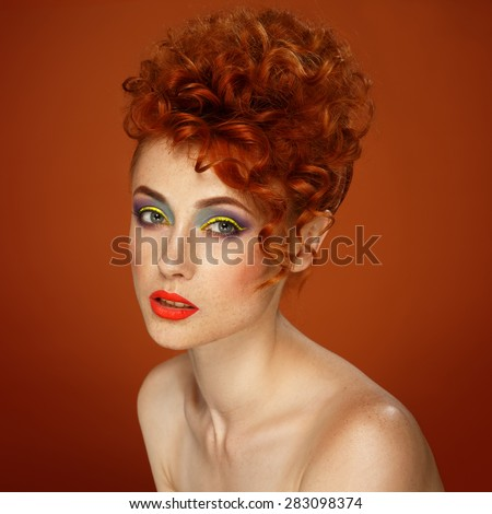 Red-haired. Beautiful girl with bright makeup. Ginger with freckles. Hairstyle. Wavy hair.