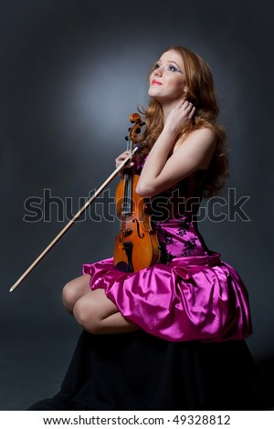 Red-haired beautiful woman sitting with blue violin