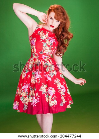 Red haired beautiful young woman, wearing a red summer dress with floral print, while posing with a wild and ingenuous facial expression, on green - stock photo