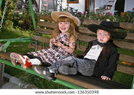 red-haired boy in a frock coat and a girl in a checkered dress. Declaration of love. - stock photo