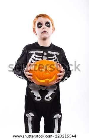 Red haired boy in skeleton costume holding a pumpkin. Halloween. Studio portrait isolated over white background   - stock photo