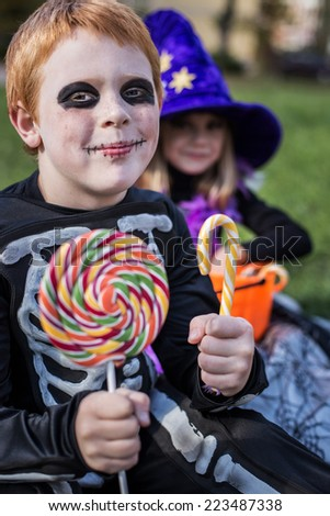 Red haired boy wearing halloween skeleton costume and holding colorful candies. Outdoor portrait - stock photo