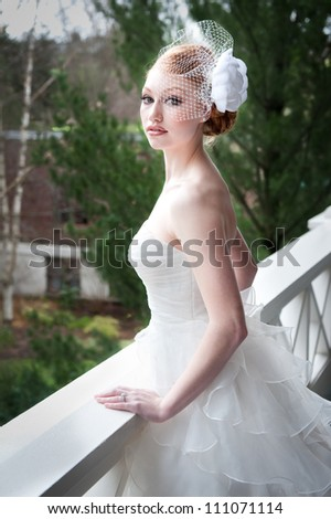 Red haired bride leans against porch railing, looking contemplative. - stock photo