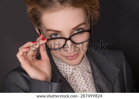 Red-haired business lady posing for photographer on dark background. Woman in grey business dress skewing at him so serious with her glasses dipped. - stock photo