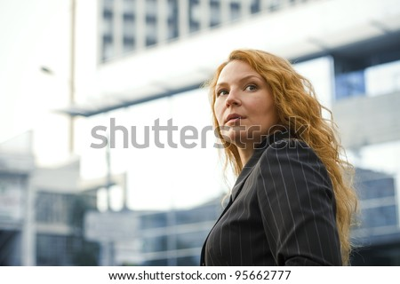 red-haired business woman leader outside the office building - stock photo