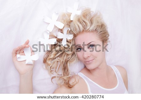 Red-haired gentle girl with daisies in hair lying on a white background - stock photo