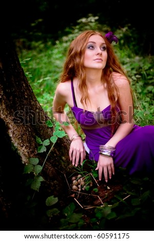 red-haired girl collecting mushrooms in wood - stock photo