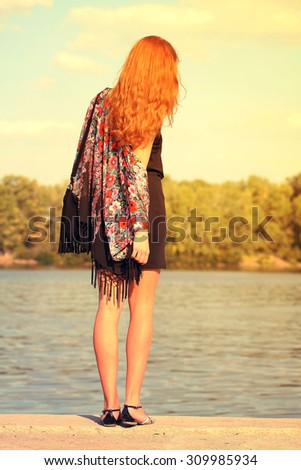 red-haired girl holding a black suede bag with fringe hands with bracelets and rings, wearing bright kimono. Boho chic style, gypsy, hippie, bohemian photo with instagram filters. - stock photo