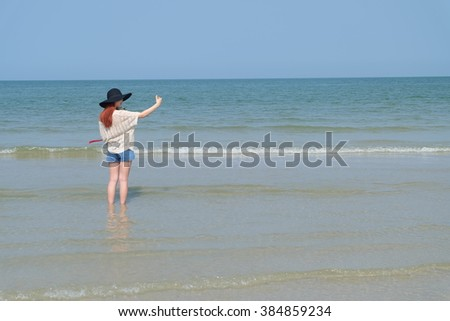 Red-haired girl holding a flower on a beach in Thailand.