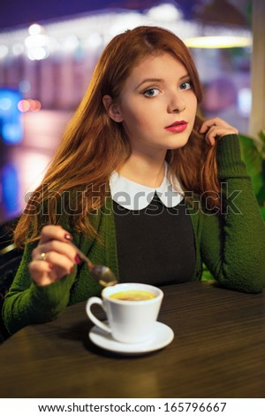 Red-haired girl in a cafe, evening shoot