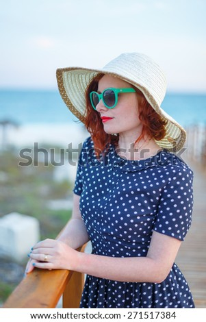 Red-haired girl in a hat and sunglasses - stock photo