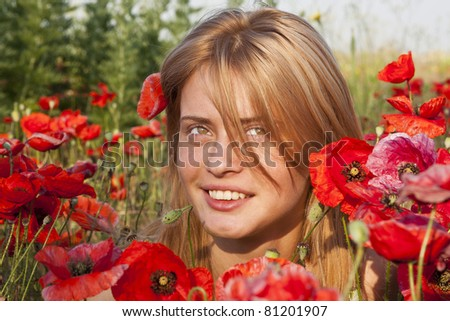 red-haired girl in a poppy field