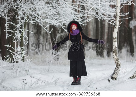 red-haired girl in coat rejoices winter, man stands in the snow, the girl in the winter forest, people laughing, glad, good mood, happiness, girl laughs - stock photo