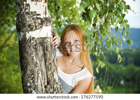 Red-haired girl in park.