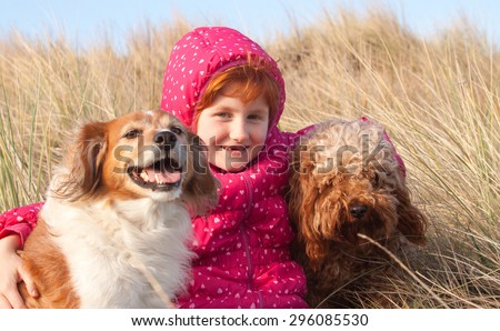 red haired girl in winter jacket hugging red haired collie type dog on a cold winter's day in grassy sand dunes at a beach in Gisborne, New Zealand  - stock photo