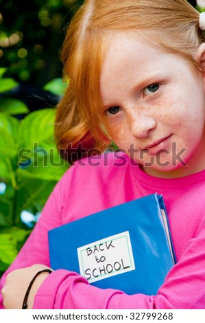 red haired girl is going back to school - stock photo