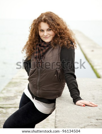 Red-haired girl near the sea. - stock photo