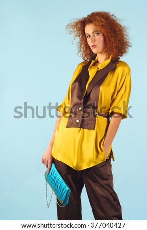red haired girl poses in yellow blouse on blue background
