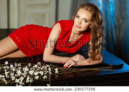 Red-haired girl with blue eyes lying on the piano with flowers