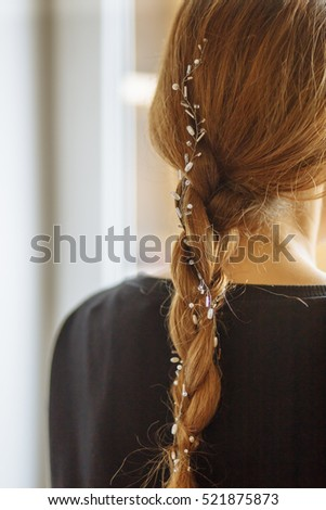 red-haired girl with braids back in a black jacket
