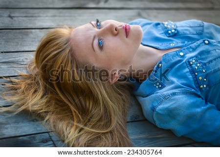 red-haired girl with bright blue eyes lying on a wooden pavement and looks at the sky. outdoor shooting. - stock photo
