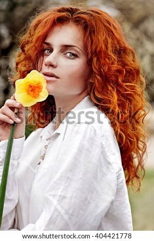 Red-haired girl with flowers narcissus. Woman portrait  - stock photo