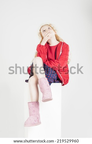 Red-haired Little Caucasian Girl Thinking and Sitting on High Pedestal. Against White Background. Vertical Image - stock photo
