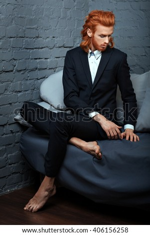 Red-haired man in a business suit sitting on the couch, he is metrosexual. - stock photo