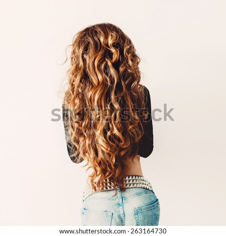 Red-haired model with luxurious long curly Hair. View from the back - stock photo