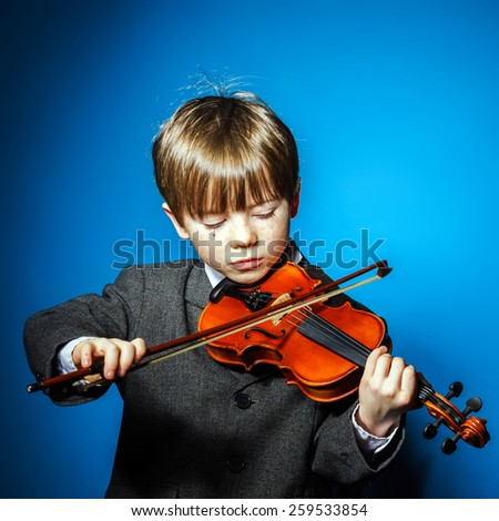 Red-haired preschooler boy with violin, isolated on blue, music concept - stock photo