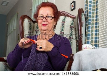 Red haired senior lady looking at you right below her glasses while crocheting her purple scarf - stock photo