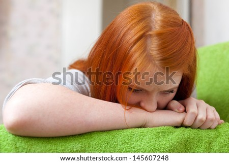 Red-haired  teenager girl  having disappointment in first love at home - stock photo
