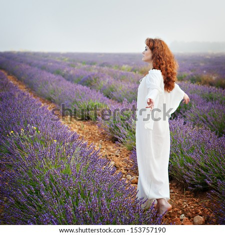 Red-haired white woman in a long white shirt on a lavender field, his back, his arms outstretched - stock photo