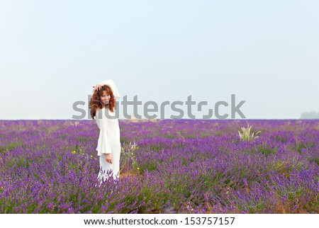 Red-haired white woman in a long white shirt on a lavender field, smiling, looking into the camera