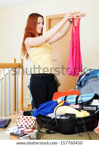 red-haired woman choosing clothes for vacation  at home - stock photo