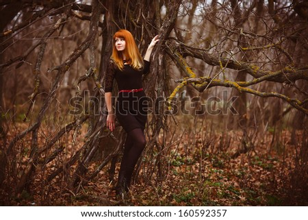 red-haired woman in black dress in a dry dark forest, dry branches on the street